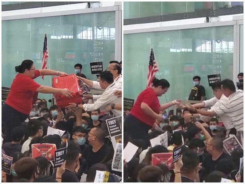 女士需要職員協助才能跨越示威者進入禁區。