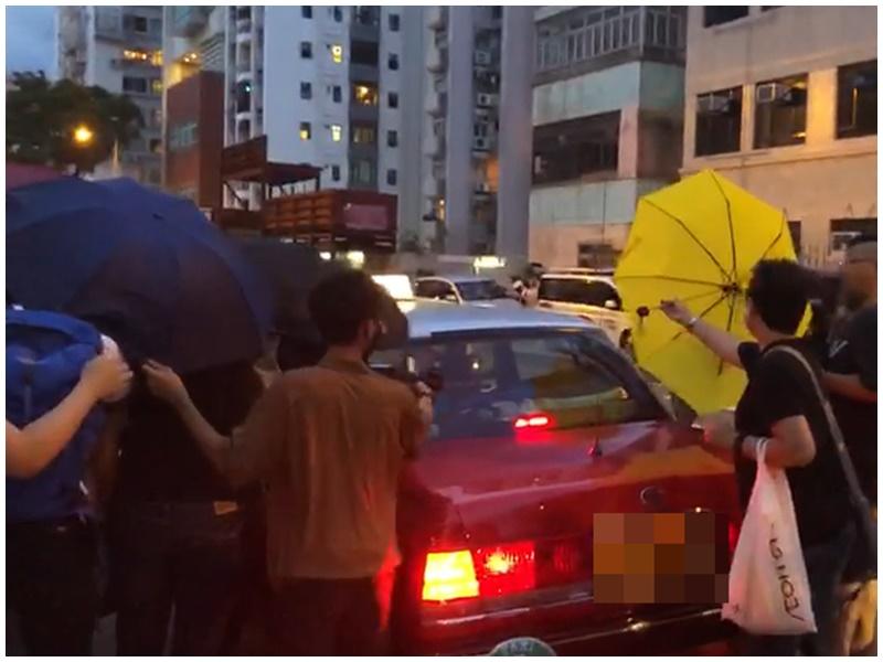 支持者撐傘保護被告上的士。
