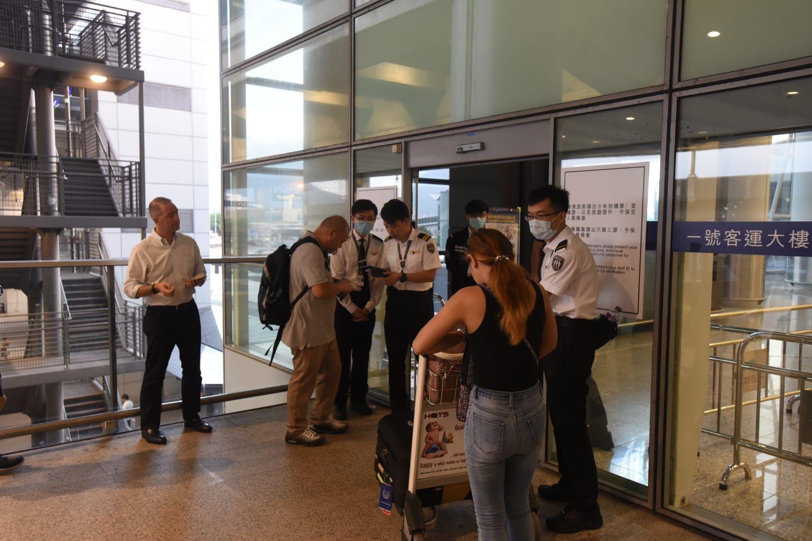 機場保安人員檢查進入大樓人士的證件及機票