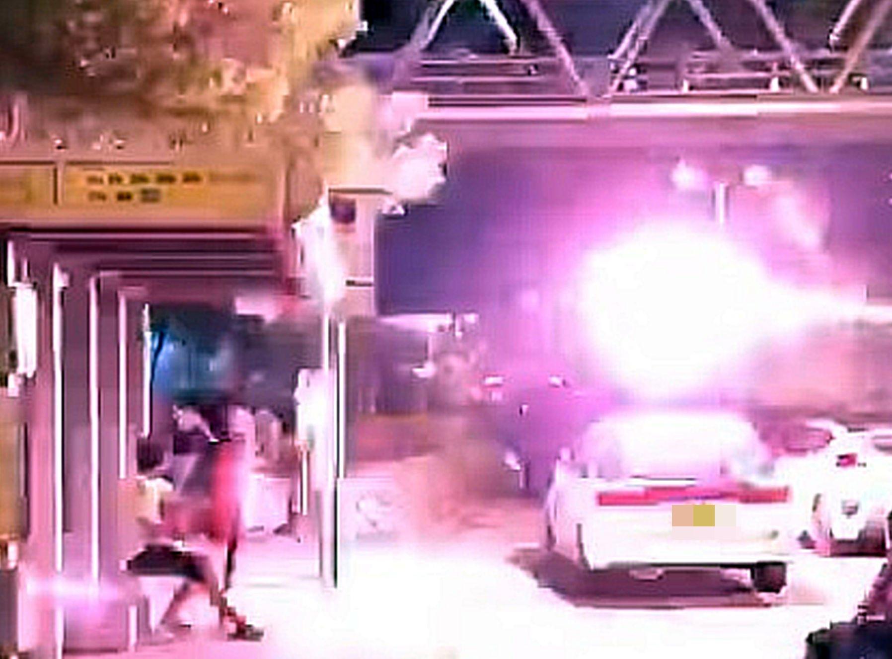 一輛私家車駛經警署,並將煙花射向聚集的人群。網圖