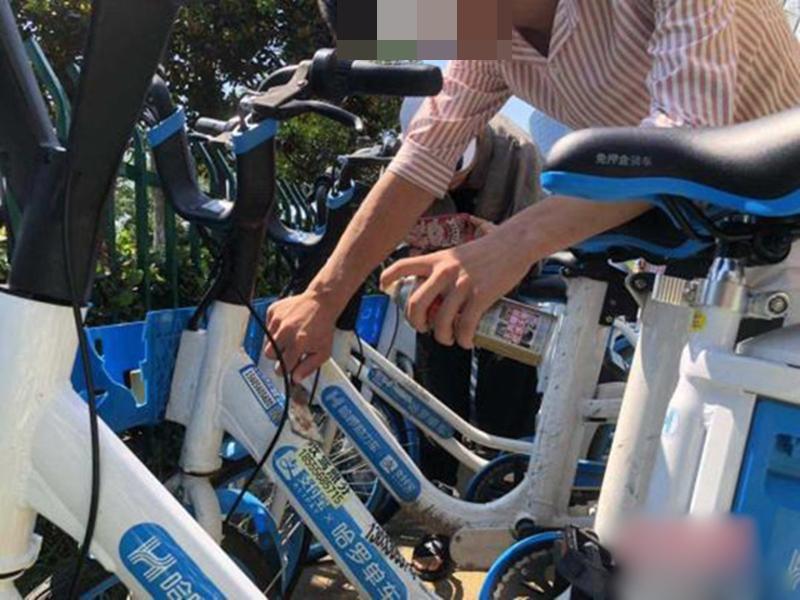 男子在企業工作人員的監督下,清理200輛共享單車上張貼的廣告。 網圖