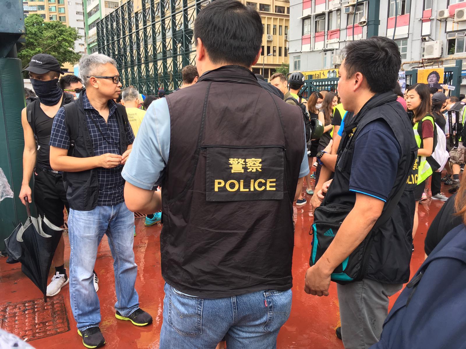 現場有穿著警察背心的人士,準備跟遊行糾察簡介及點人數。