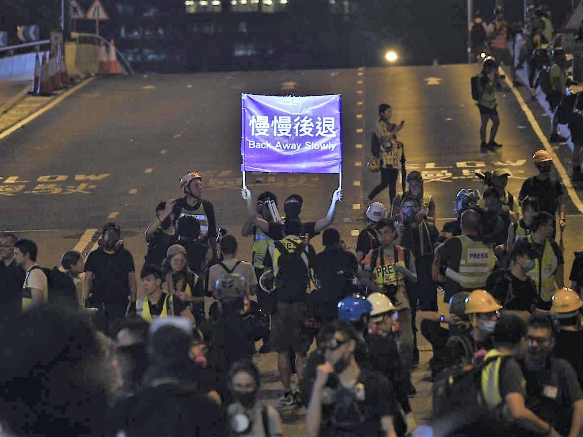 有人高舉「慢慢後退」標語,呼籲市民離開。