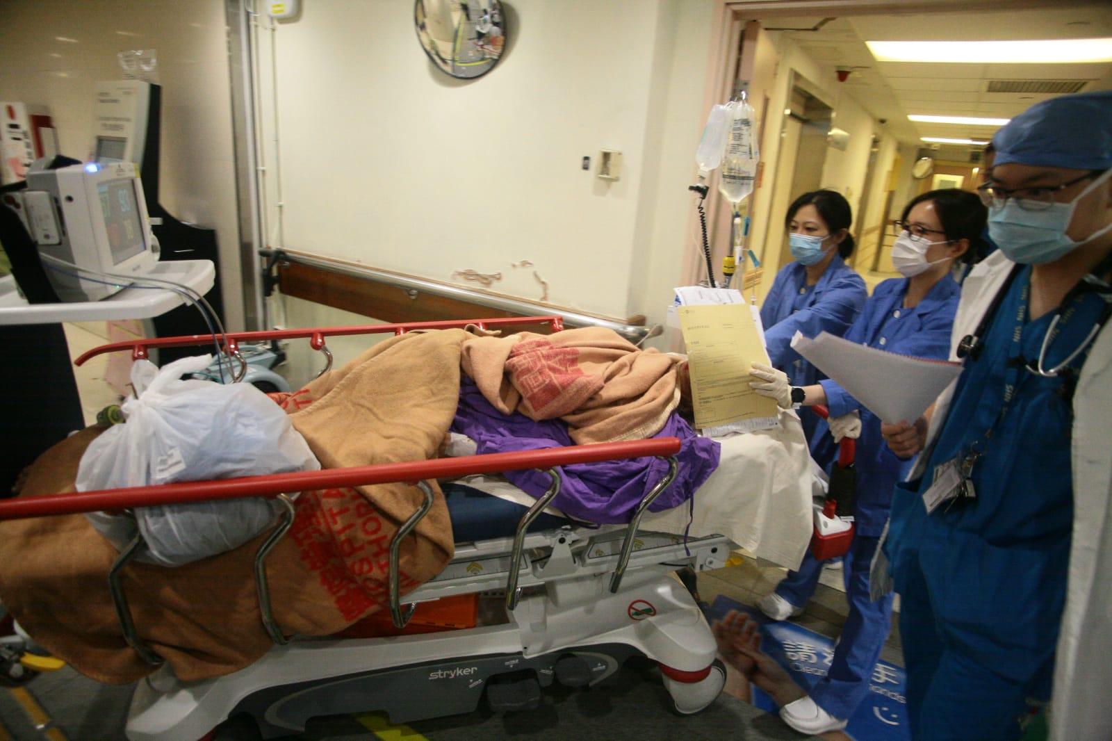 男傷者在瑪麗醫院急症室搶救後,由醫護人員推上病房。