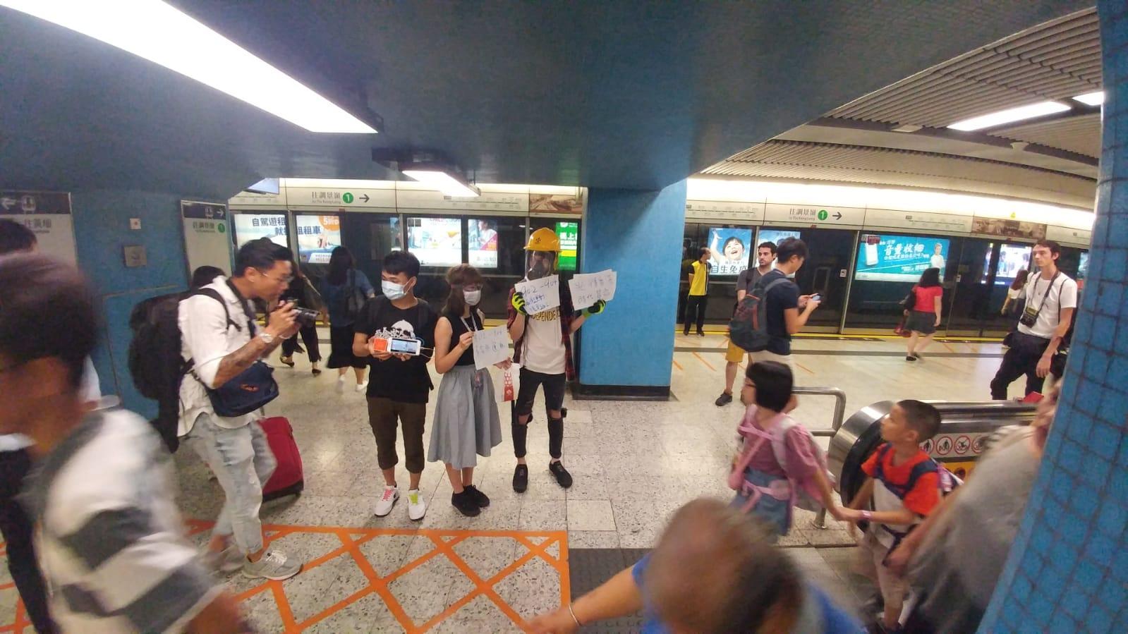 有年輕人在站內向乘客展示寫有「毋忘元朗721」、「五大訴求,缺一不可」的標語。