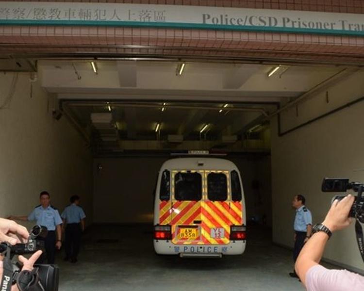 兩名被告由警車押上法院。