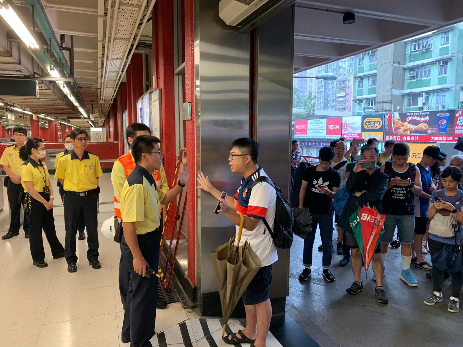 男子在鐵閘下與職員理論。
