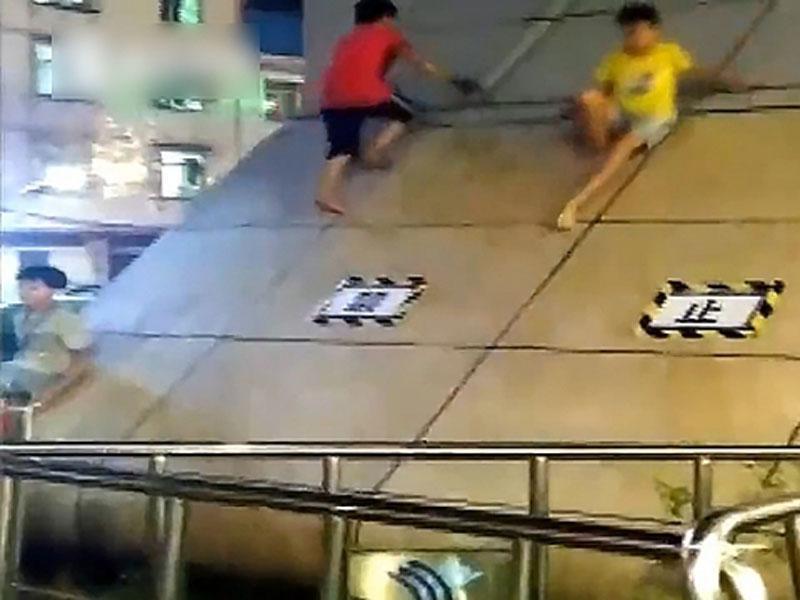 頑童將南寧一個地鐵站出入口的斜坡,當成滑梯,無視禁止攀爬的告示。(網圖)