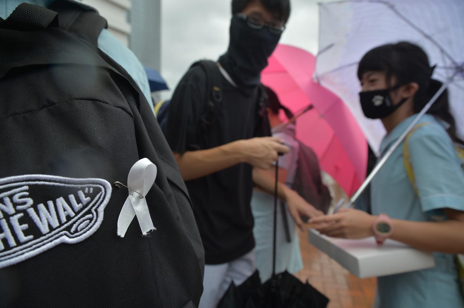 有學生扣上白絲帶。