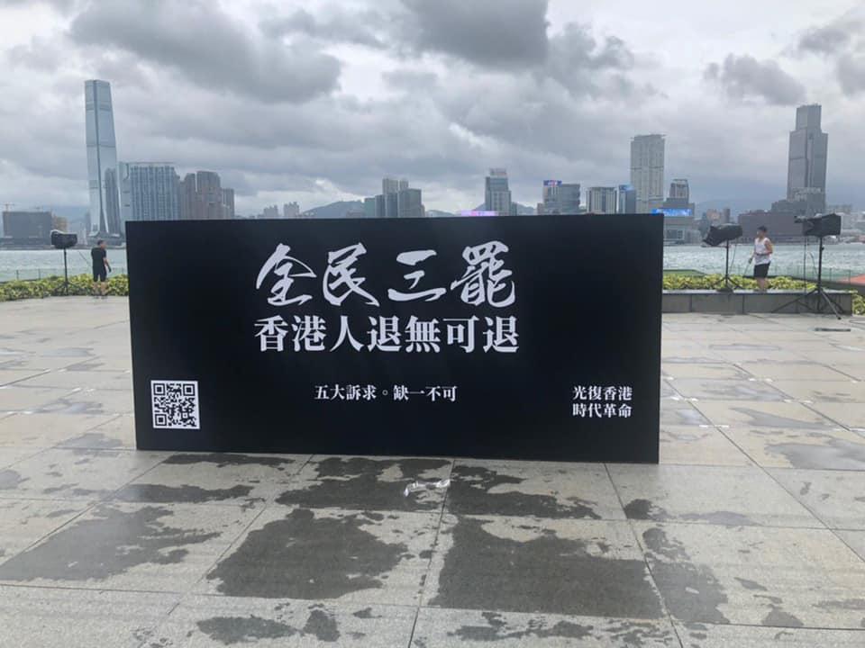 主辦單位在添馬公園放置「全民三罷香港人退無可退」的黑色大台標語。 罷工FB圖