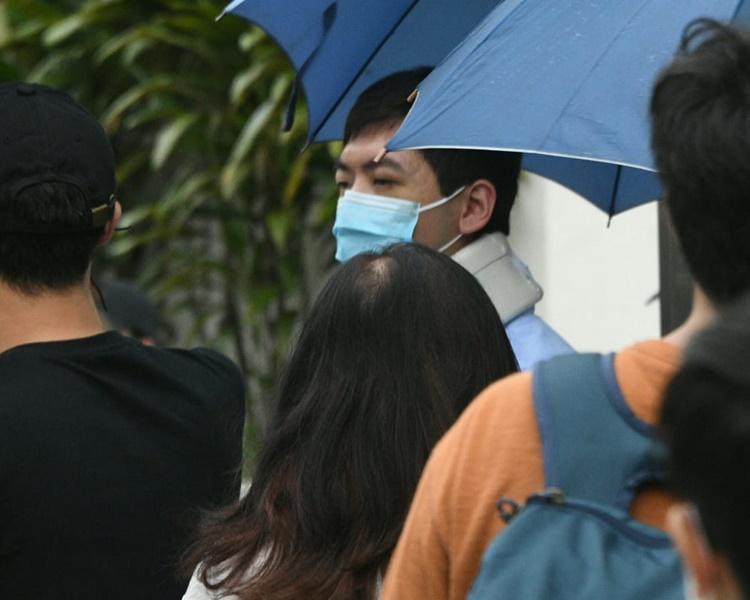 周健豪在多人撐傘下保護地離開法院。