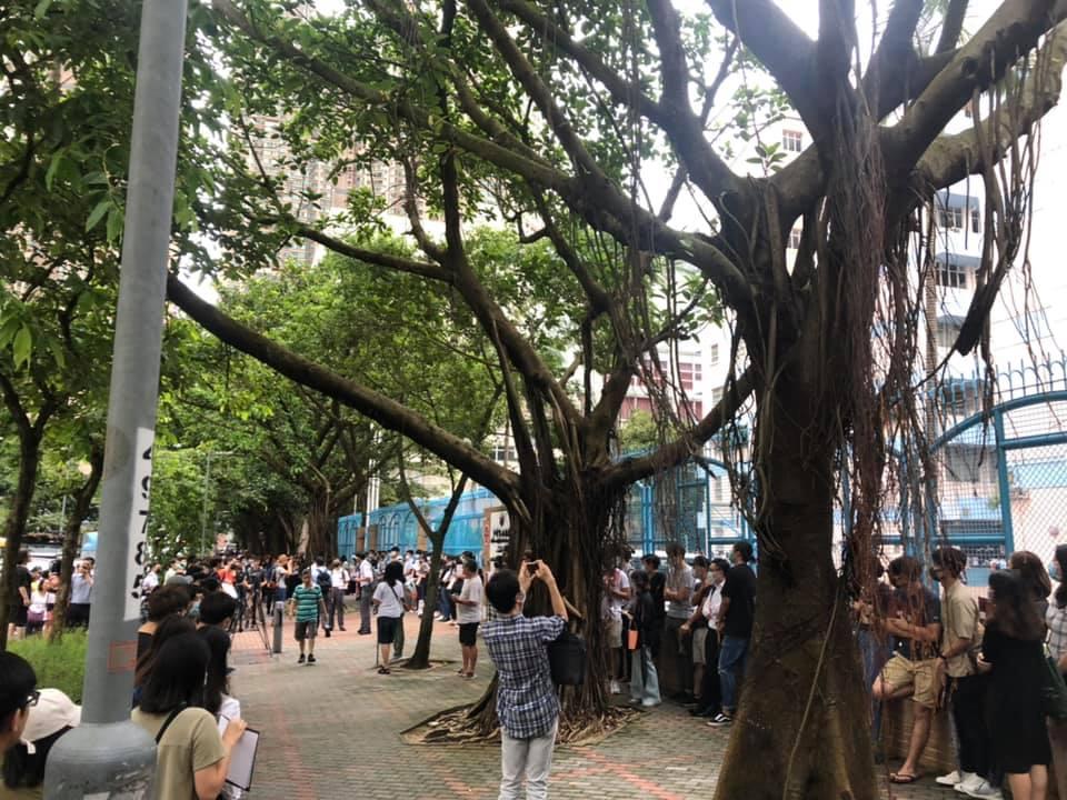 一批學生戴口罩手持手持標語在校門外默站。 東區社區幹事蔡志強FB圖