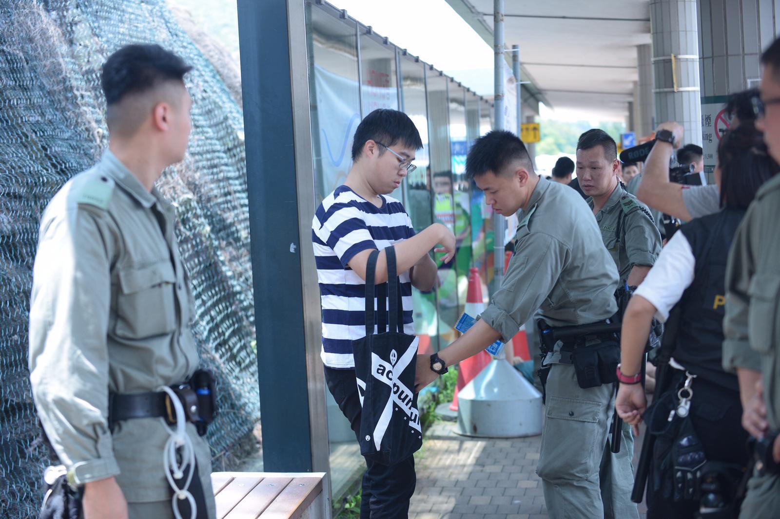 警員搜查乘客的隨身物品。