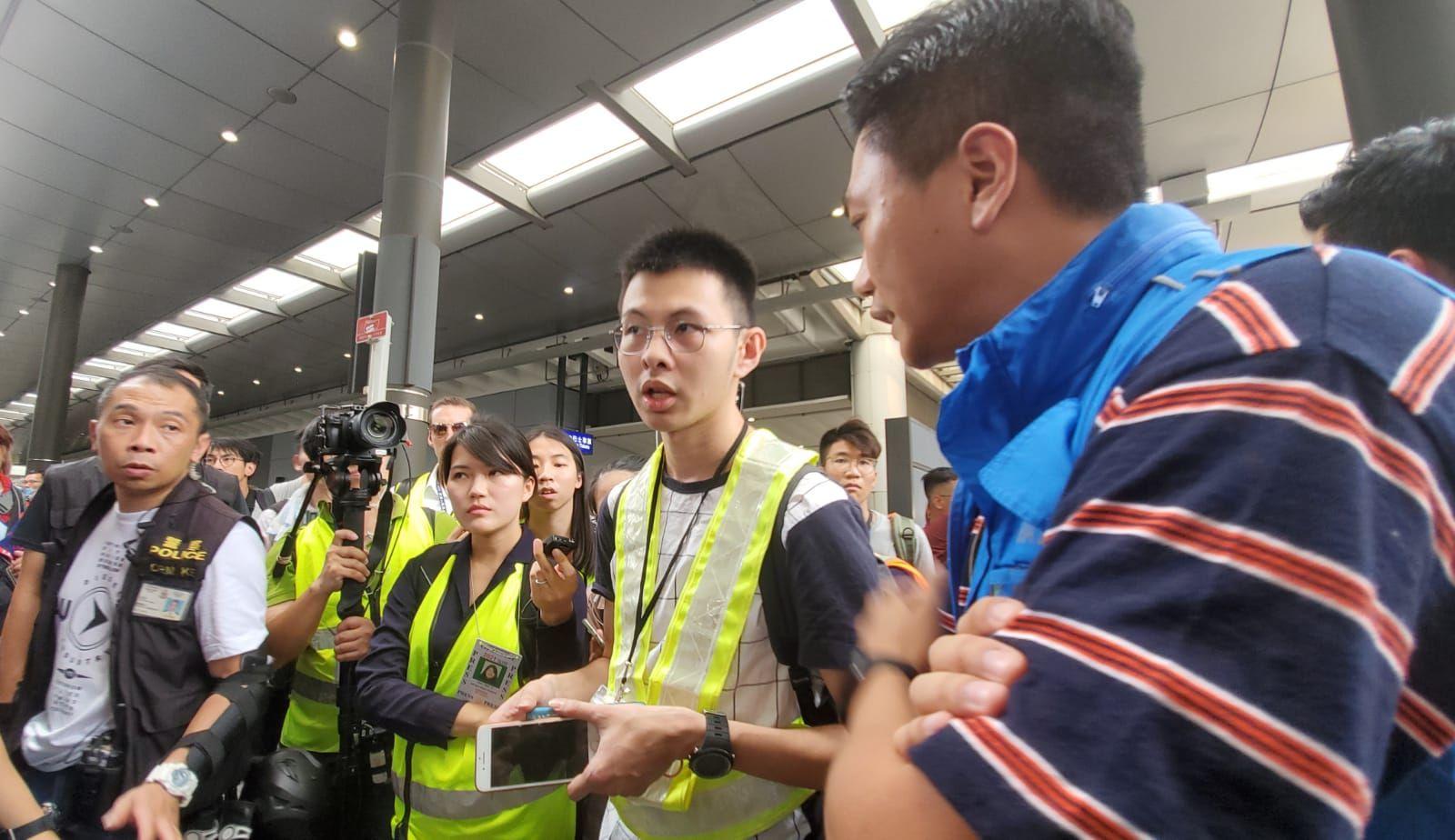 警方向在場一名身穿反光衣的男子查證其記者身份。