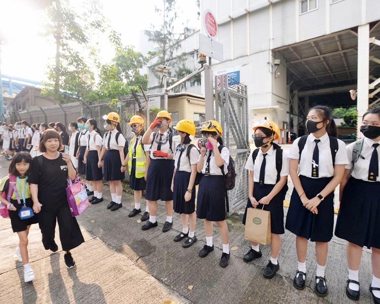 慈雲山學校區的人鏈,有學生戴上頭盔和防毒面罩參與活動。