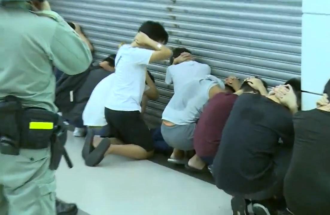 警員要求可疑人士一字排開蹲下。無綫新聞截圖