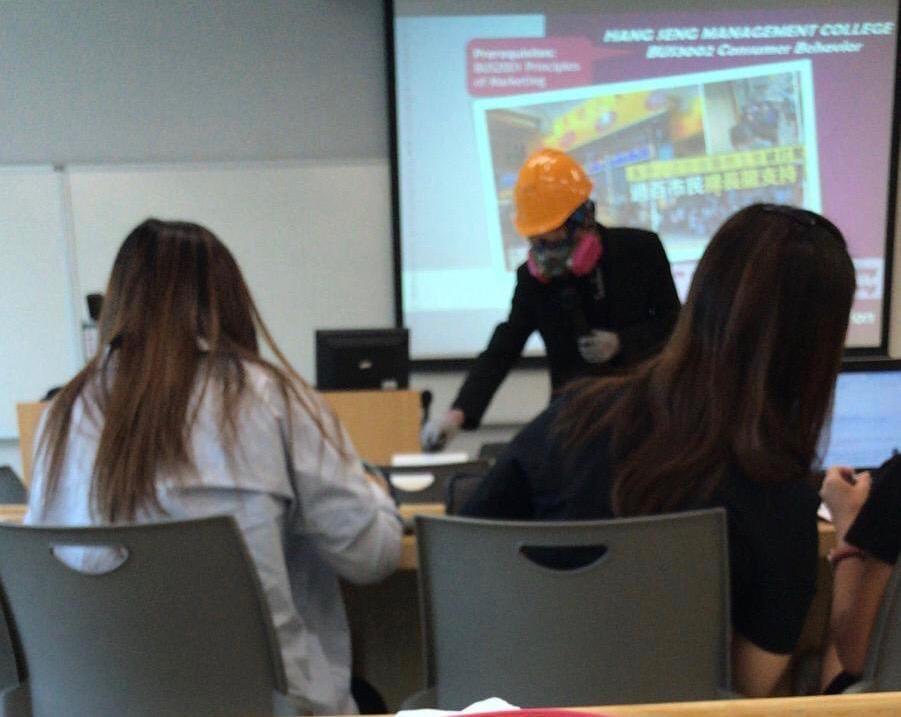 該名教師身穿黑衣,戴上頭盔和「豬嘴」口罩上課。網民Caidy Ng