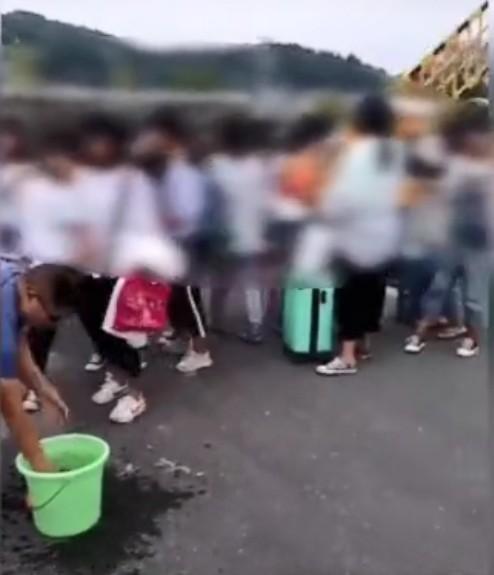 有男老師在校門以抹布為女學生「強制卸妝」。影片截圖