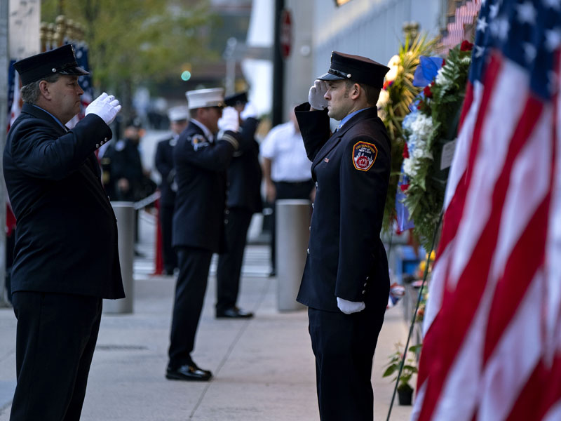 紐約市消防隊員在一個世貿中心旁邊的消防站和911紀念站點旁邊的紀念碑前致敬。AP