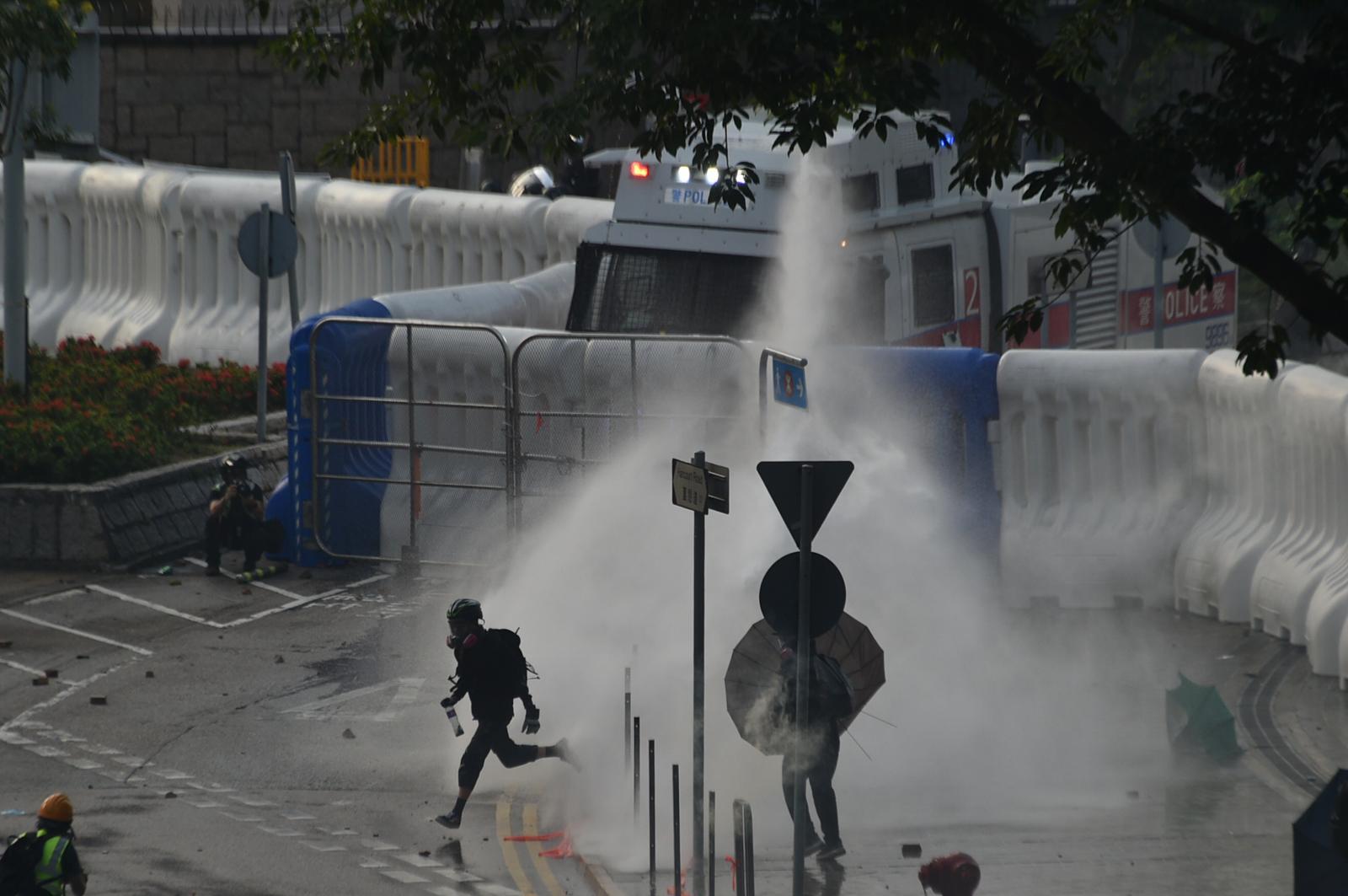 水炮車向人群發射水炮。