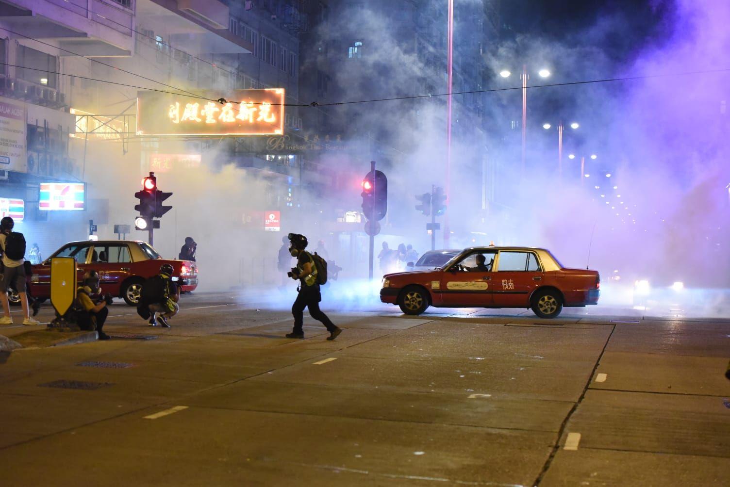 警方發射催淚彈時,現場仍有不少汽車在路中心。