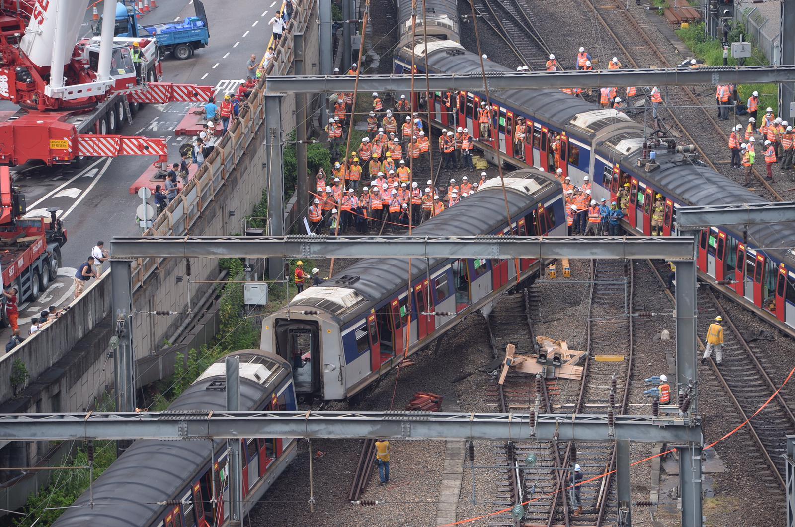 港鐵工程人員正將出軌的車廂吊起並扶正。