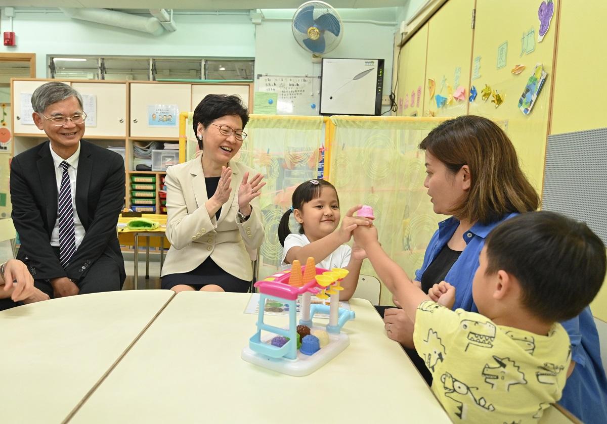 林鄭月娥(左二)及羅致光博士(左一)視察學童上課的情況。政府新聞處