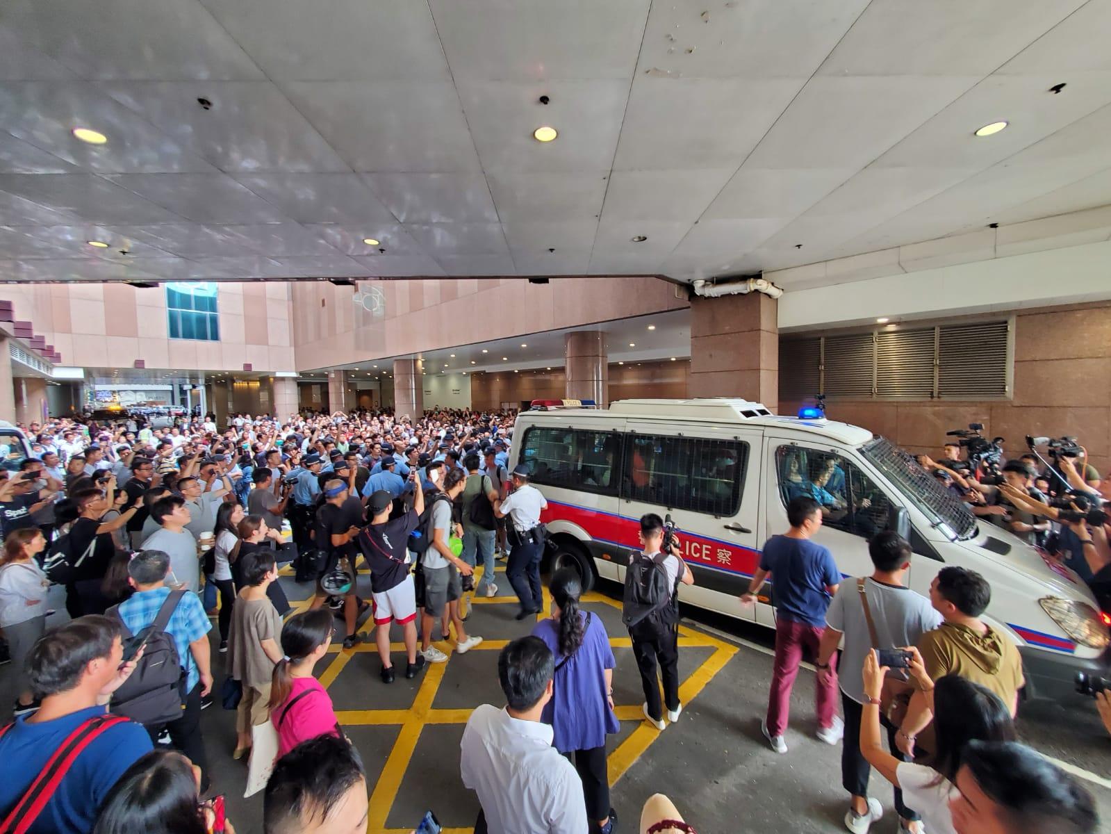 多名愛國人士由警方護送上警車離開。