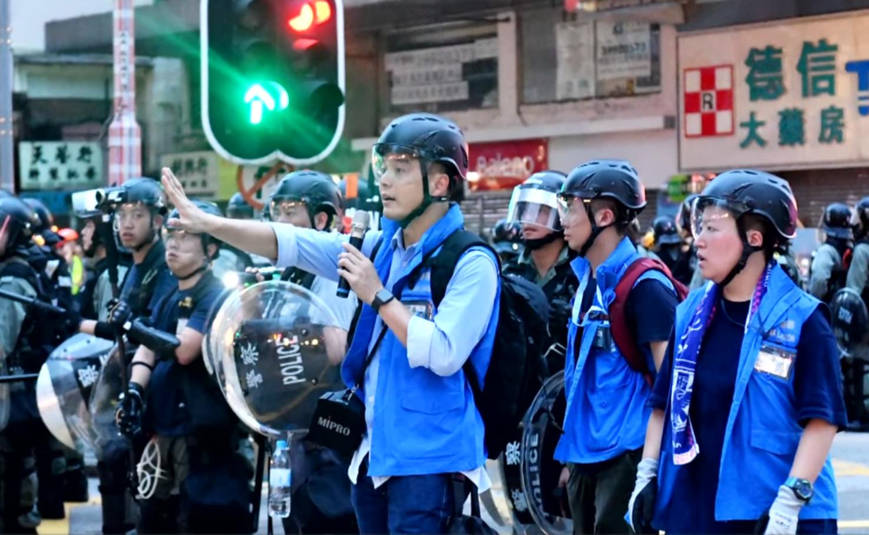 平日另一個工作,就是穿起藍背心到示威現場,要求記者給予「工作距離」給予警方。影片截圖
