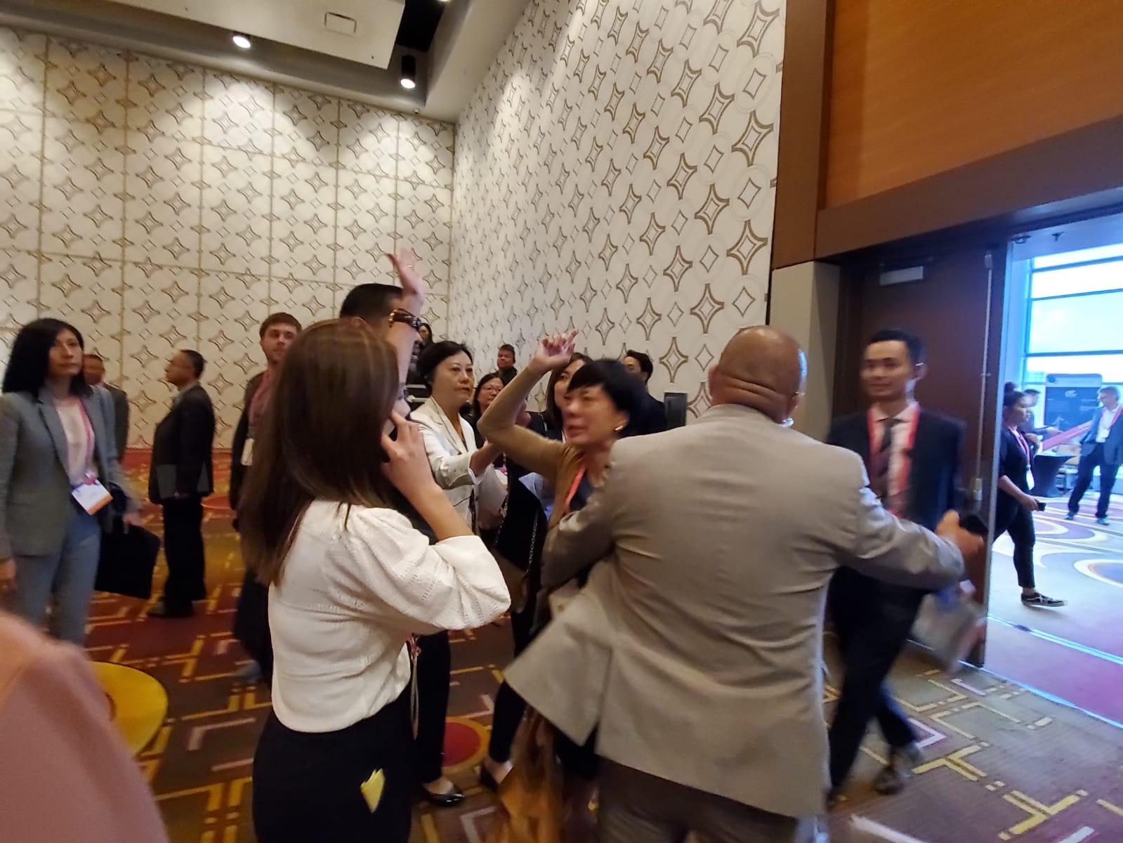 三名与会华人,在场内高叫「光复香港,时代革命」、「Democracy Now」被保安拉离场。