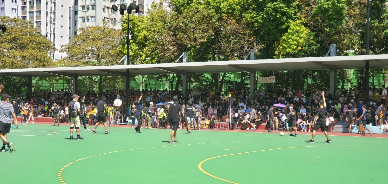 參加遊行的人士在球場看台附近集合。
