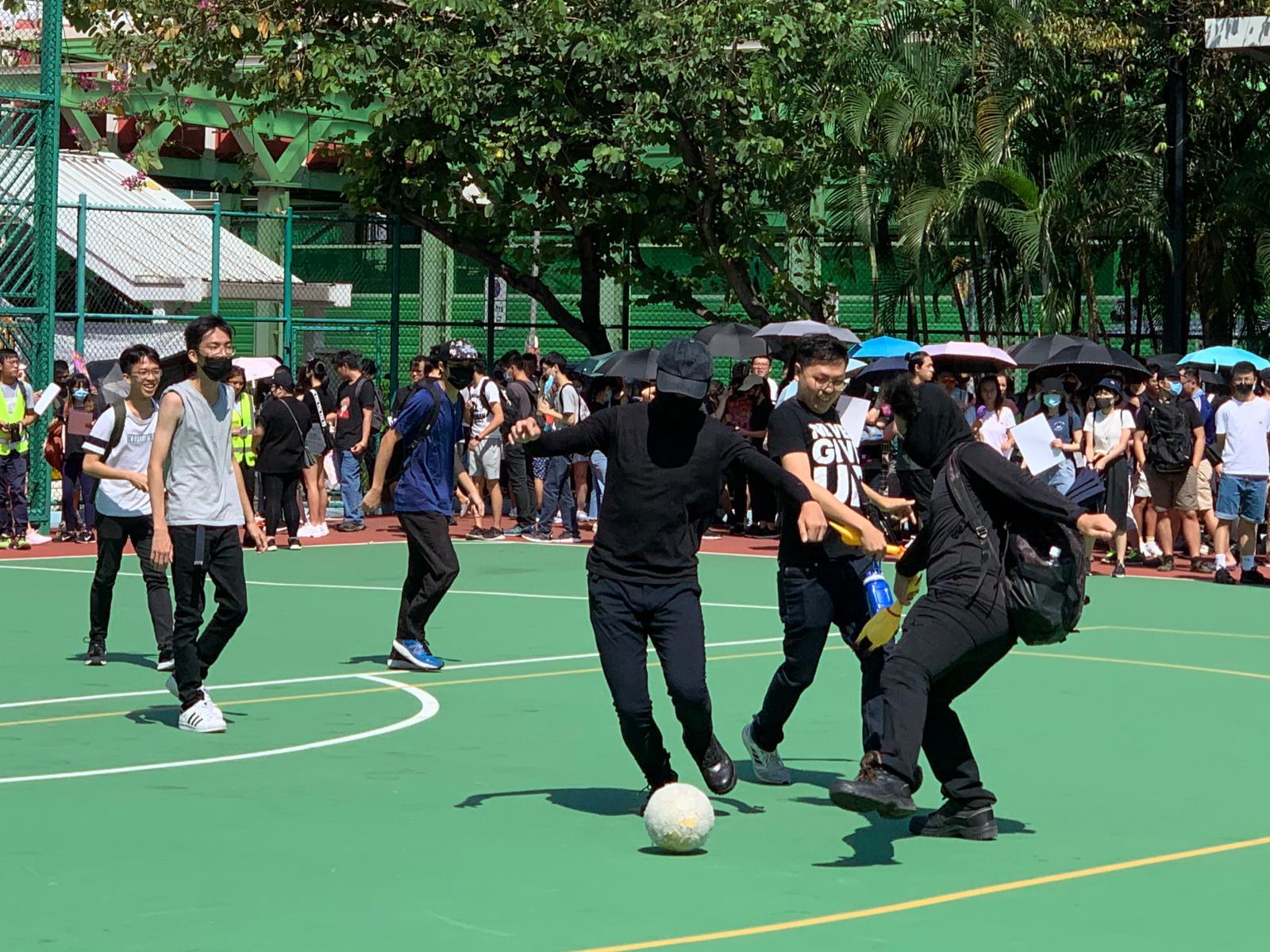 有戴口罩的黑衣人在起步前先在球場內踢波。