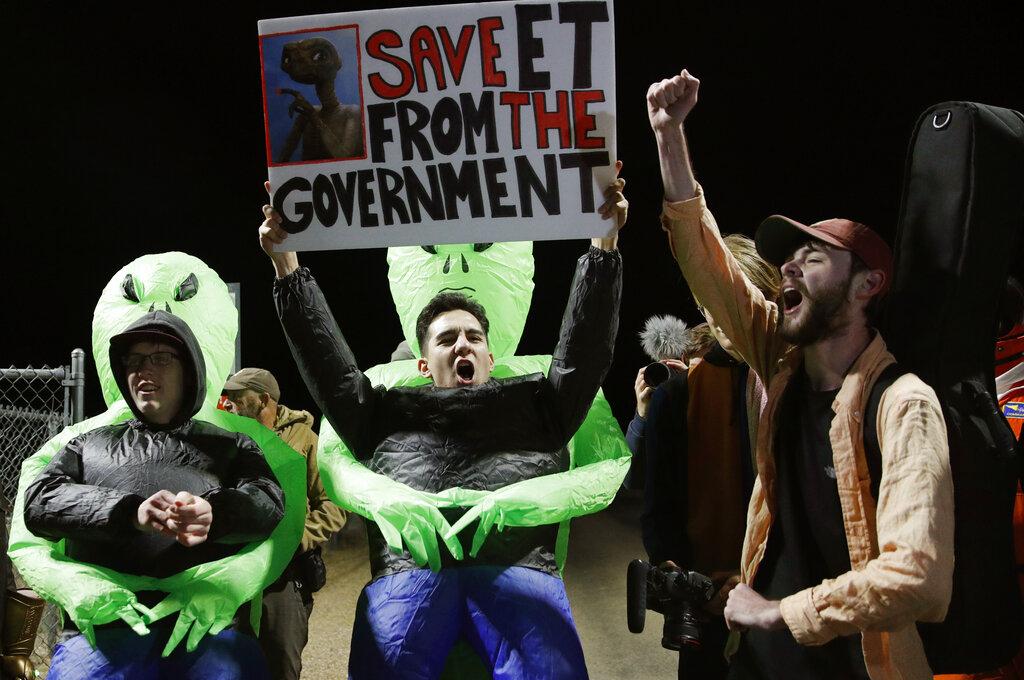 部分民眾戴著錫紙帽及外星人面具,其他人士手持標語,上面寫著「把外星人從政府釋放出來吧!」AP