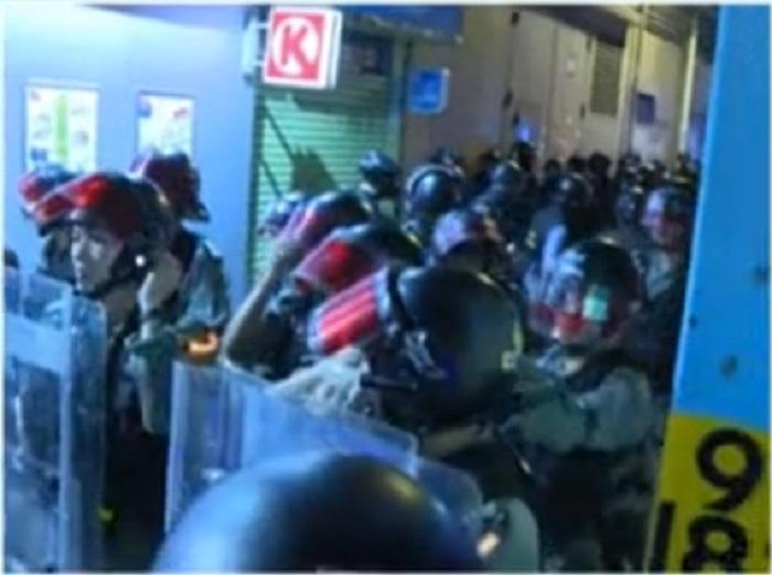 大批防暴警察在一家便利店外戒備。有線截圖
