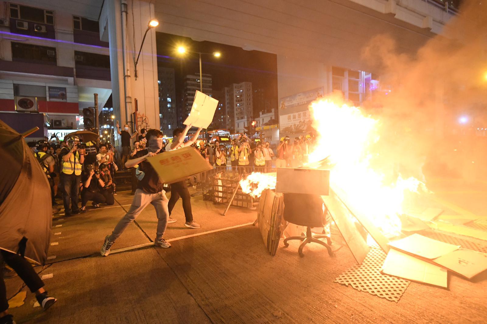 示威者不斷將雜物擲向火堆。