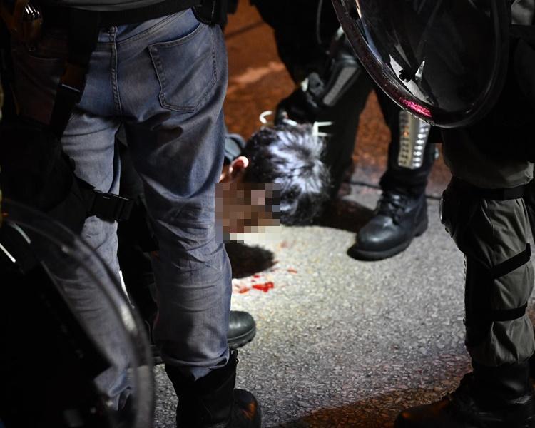 紅衣男被制服,地上沾有鮮血。
