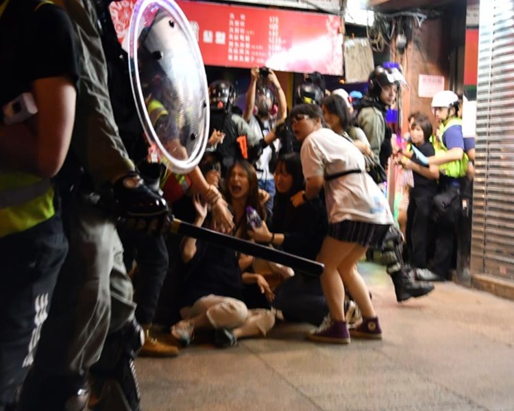 有市民跌倒在地上,在旁人士與警察理論。