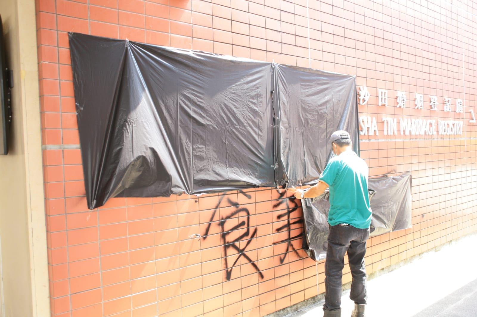 外牆遭人噴寫字句塗鴉,職員用黑膠袋遮蓋。楊偉亨攝