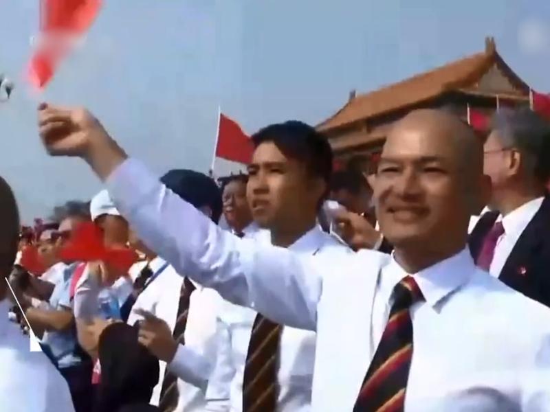直播中出現「光頭劉sir」在觀禮台上奮力揮舞國旗的畫面。 網圖