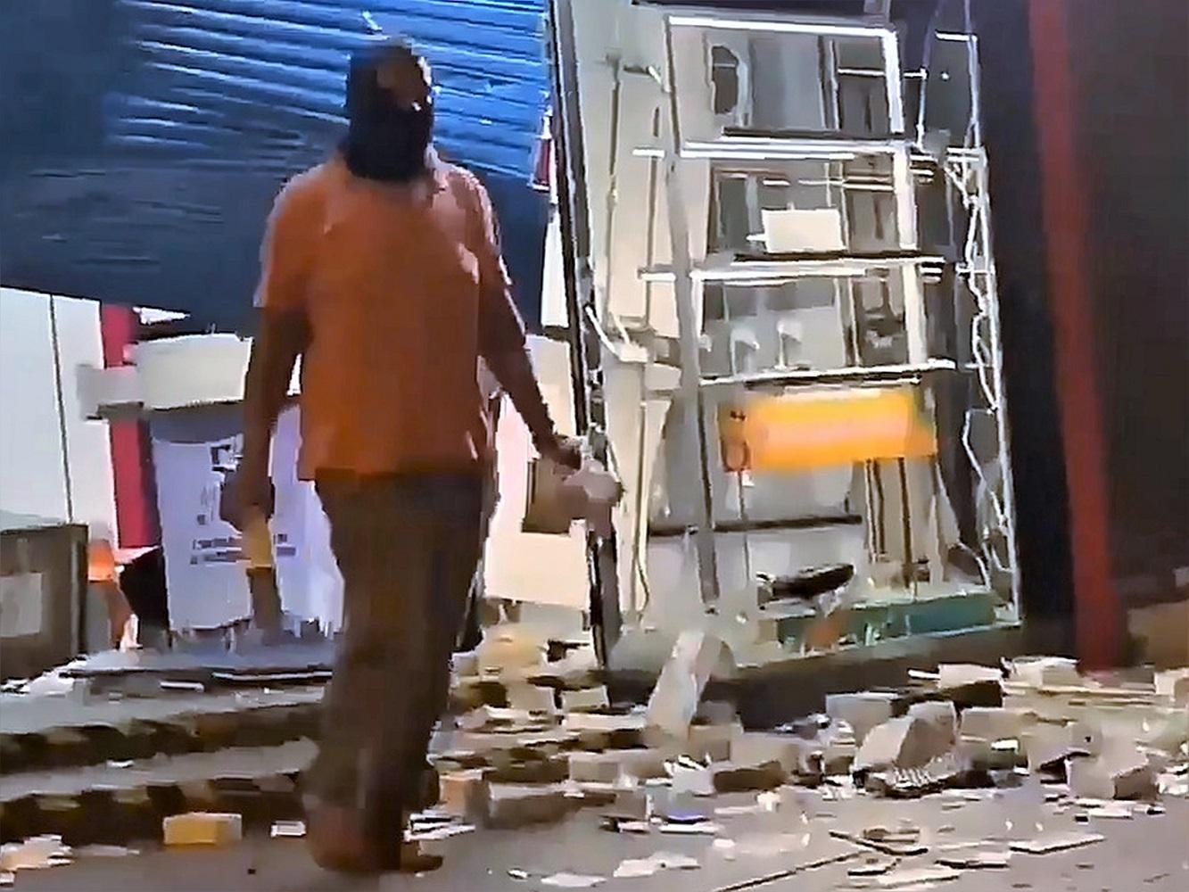 有南亞裔人士趁火打劫,掠去電訊商店內的手機。網圖
