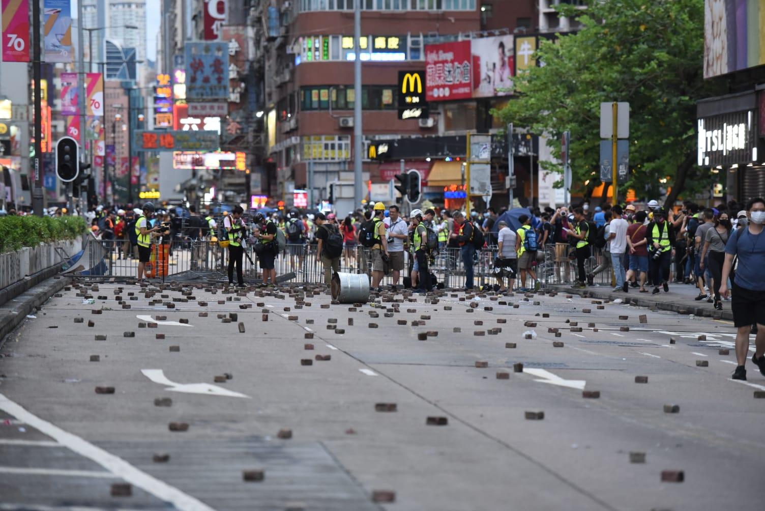 示威者投擲磚頭。黃文威攝