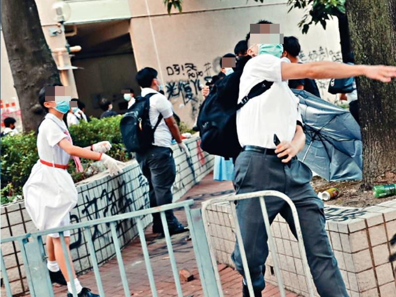 有身穿校服、戴上口罩學生向學校外牆投擲雞蛋等物品。路透社