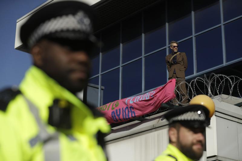 一名身穿棕色上班服装的男子爬过铁丝网,到这个伦敦东部机场的入口屋顶上拉横额,其后遭警方带走。