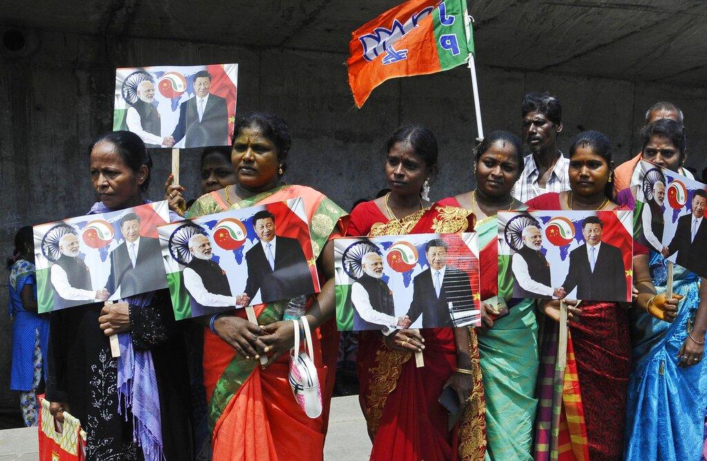 印度民衆手舉習近平和莫迪照片。AP