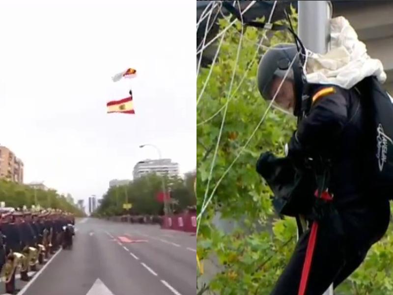 西班牙國慶閱兵上,傘兵攜帶國旗從天而降,向前來觀禮的國王致敬,惟撞上一旁路燈並掛在上面。(網圖)