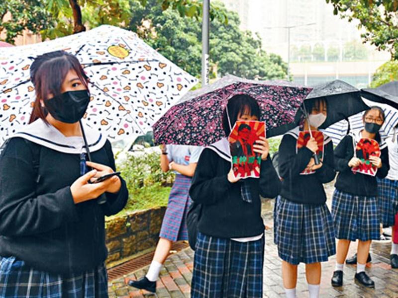 逾二十名學生與數十名自稱校友昨響應網上號召,冒雨在校門外築成人鏈抗議。