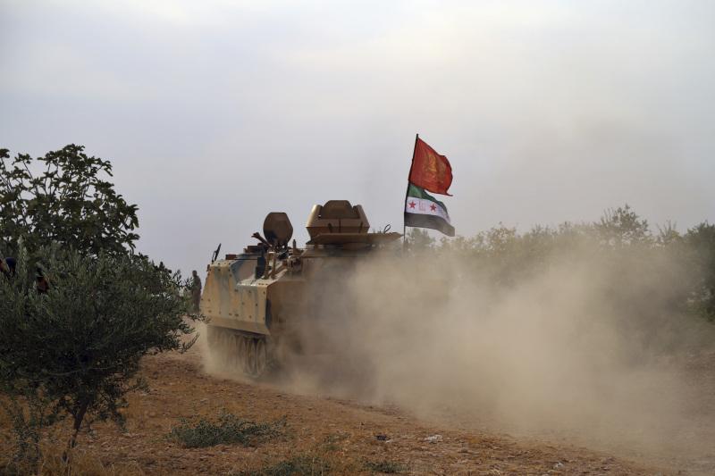 敘利亞部隊在俄軍支援下,開入美軍早前撤離的城鎮曼比季,並在城郊建築物升起兩國國旗。AP