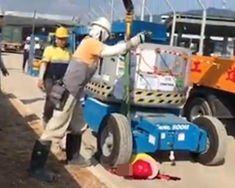 影片可見,一名女工被壓在一輛升降台工程車的左後轆下。香港突發事故報料區 網民Catherine Cheung