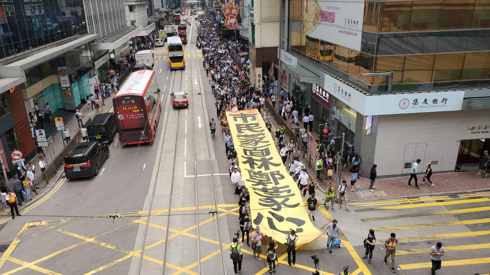 示威者帶同巨型直幡走出遮打花園,沿馬路遊行,阻礙行車線。