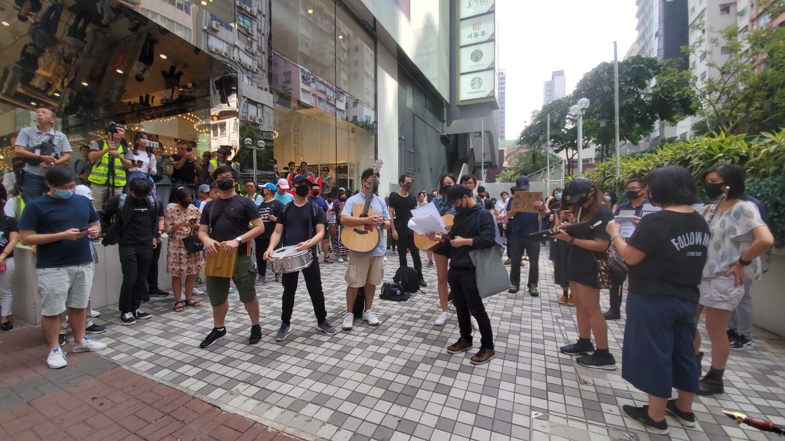 一批示威者在朗豪坊外演奏樂器及唱歌後起步遊行。